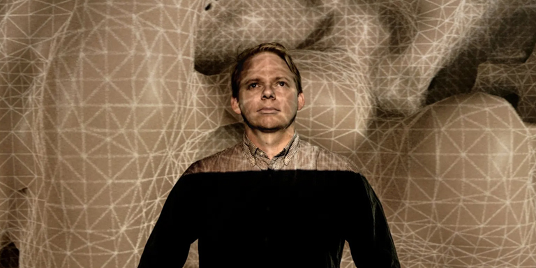 Baden Pailthorpe standing in front of his work Clanger, a projected topology of gridded land forms